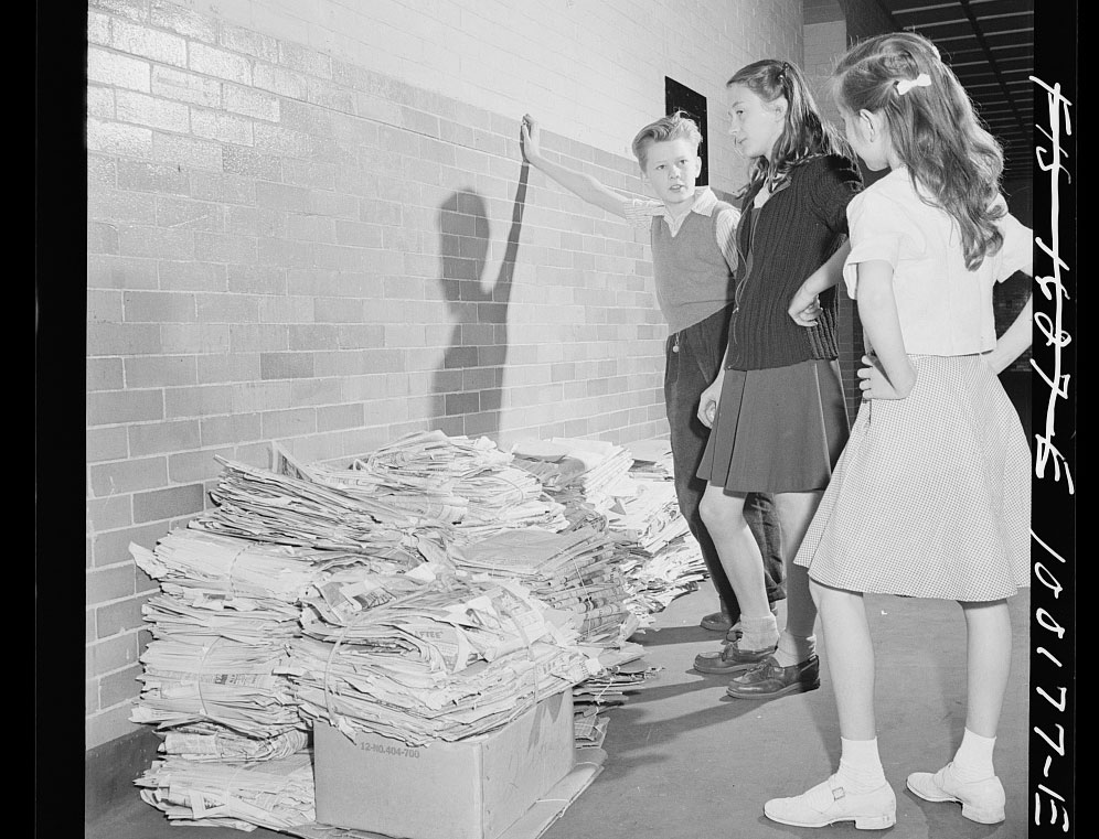 A 1940s photos of students standing over a pile of scrap paper