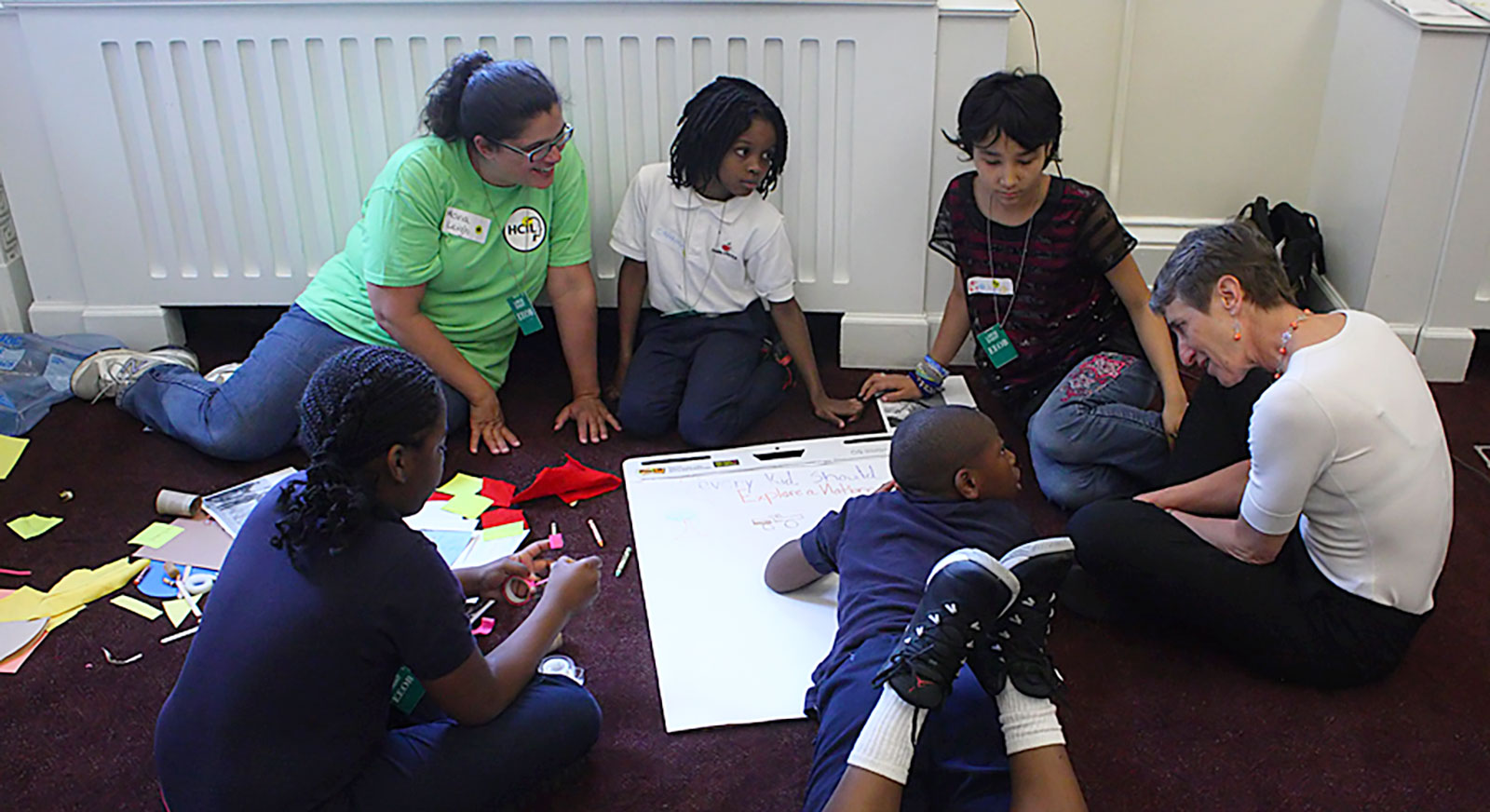 Children and adults sit around a large piece of paper while co-designing the Every Kid in a Park website.