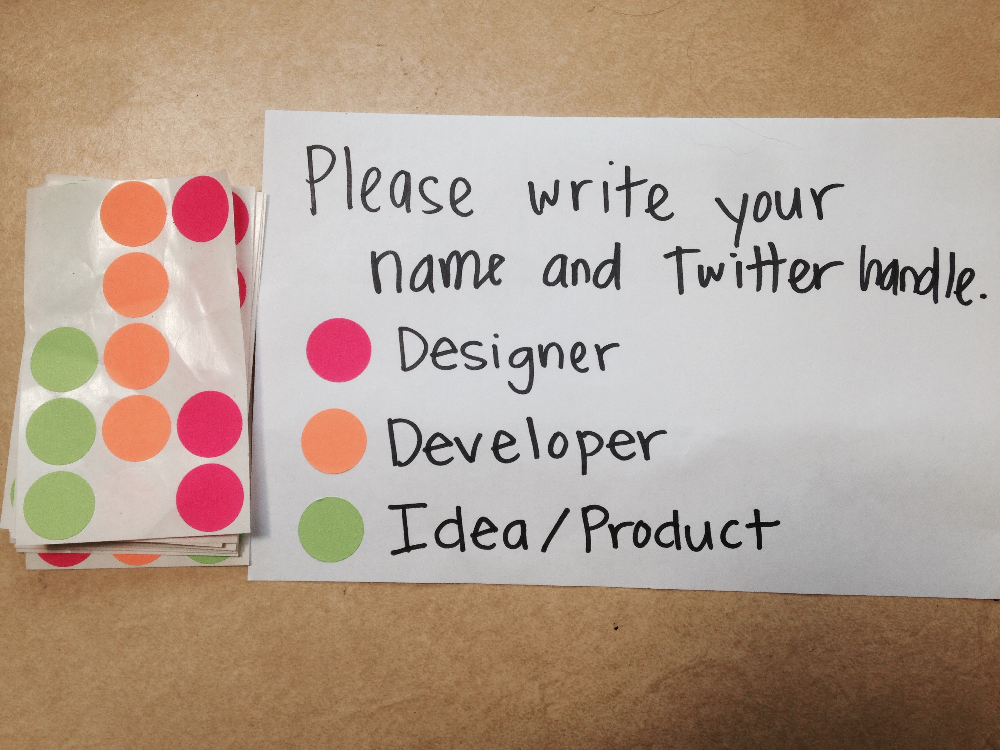 Image: nametag from recent hackathon showing color-coded stickers for devs, designers, and content strategists