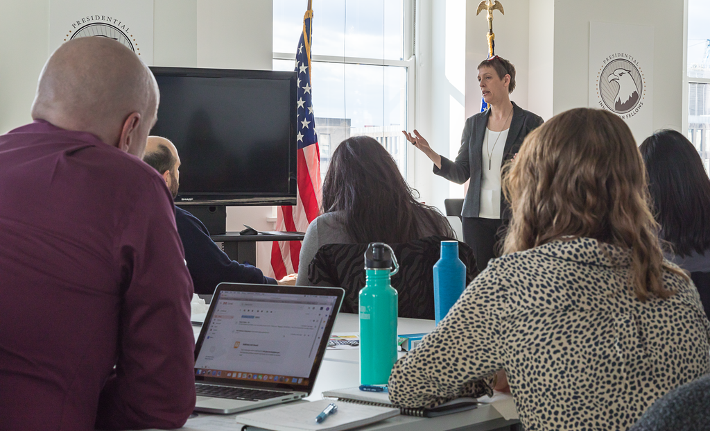 A photo of Acting Executive Director of 18F, Angela   Colter, addressing the new group of Presidential Innovation Fellows in   January 2019.